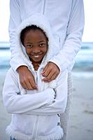 Mother with arms around daughter 7-9 on beach, smiling, portrait