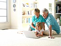Grandparents with granddaughter 6-8 using laptop computer on floor, smiling