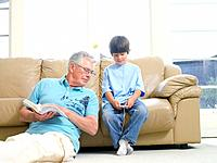 Grandfather with book looking at grandson's 7-9 MP3 player