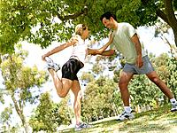 Young couple stretching in preparation for running, smiling at each other tilt