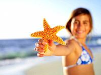 Girl 3-5 with starfish on beach, close-up of hand
