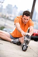 Male runner stretching on pavement tilt