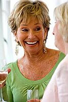 Senior woman with glass of wine, smiling, close-up