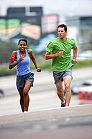 Couple running outdoors, portrait of woman