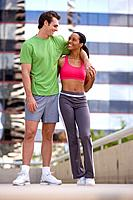 Young couple in exercise clothes, smiling at each other