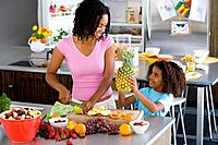 Woman making fruit salad with daughter 6-8