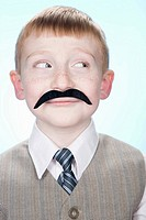 Portrait of a boy wearing a fake moustache