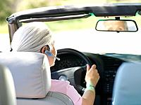 Woman with hands-free device in car, rear view