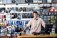Shop assistant behind counter, smiling, portrait