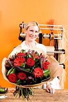 Female florist with bouquet of flowers, smiling, portrait