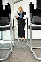 Businesswoman with paperwork in meeting room, low angle view