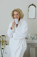 Woman having coffee in bathroom