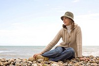 Woman sitting on pebble beach