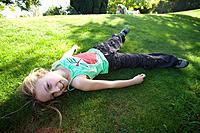 Girl 8-10 laying on grass, portrait