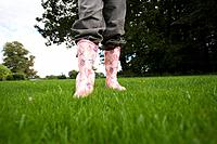 Girl 8-10 in wellington boots on grass, low section