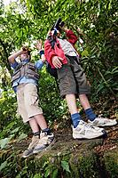 Children using binoculars in woods