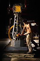 Bare chested Asian man working in factory