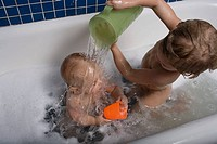Boy pouring water over baby brother