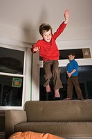Boys jumping off sofa