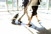 Businessman and woman with luggage, low section blurred motion