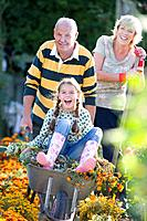Senior couple gardening, granddaughter 7-9 in wheelbarrow, portrait
