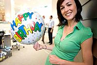 Woman with 'Happy Birthday' balloon, smiling, portrait