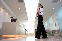 Businesswoman by reception, portrait, low angle view