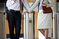 Business people using mass transit turnstile