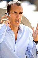 Businessman using hands-free cell phone headset