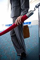 Businesswoman next to velvet rope in airport