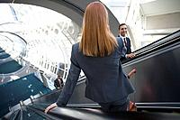 Business people using escalators in airport