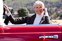 Senior woman posing with red convertible (thumbnail)