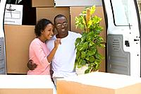 Couple unloading boxes from van