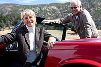 Couple posing in red convertible
