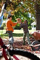 Brother and sister throwing autumn leaves