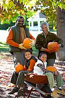Grandparents and grandchildren holding pumpkins in autumn