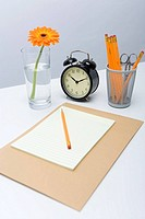 Pencil on top of document with clock and jar in background