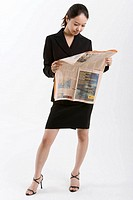 Businesswoman looking at newspaper