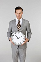 Businessman holding a clock, portrait