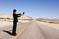 Man with laptop standing on country road, side view