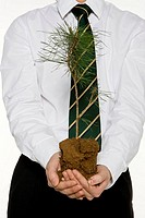 Businessman holding plant, close_up