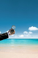 Businessman holding compass by sea, close_up