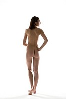 Naked woman standing with hand on hip, rear view