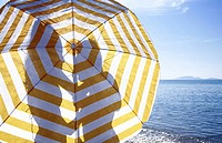 Silhouette of couple on the beach behind umbrella