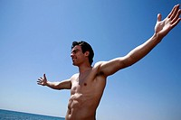 Male young adult on beach spreading arms (thumbnail)
