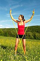 young woman doing exercises with a stretch band on a grassland
