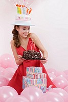 Young woman holding birthday cake, looking down