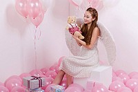 Young woman sitting on block amid pink balloons, holding teddy bear