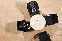 high angle view of group of business people sitting around conference table