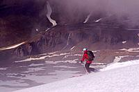 A woman skiing on a glacier above the clouds on Mount Vsesevidov in the Aleutian Islands in Alaska
